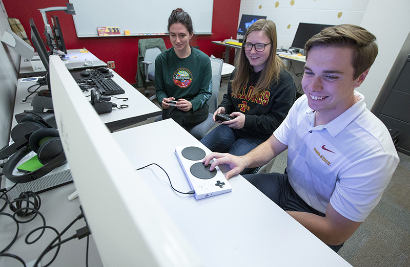 Three students play Xbox with an adaptive controller and two typical controllers in the digital accessibility lab.
