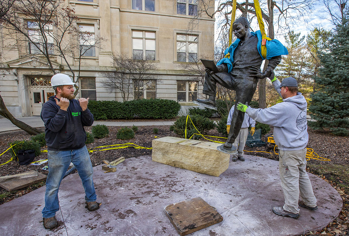 Crews lower the bronze Jack Trice sculpture to its new home north of Beardshear Hall