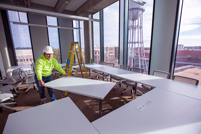 worker moves conference table into place