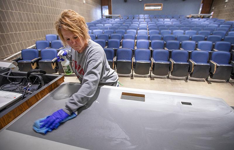 custodian disinfects a teaching table in an auditorium