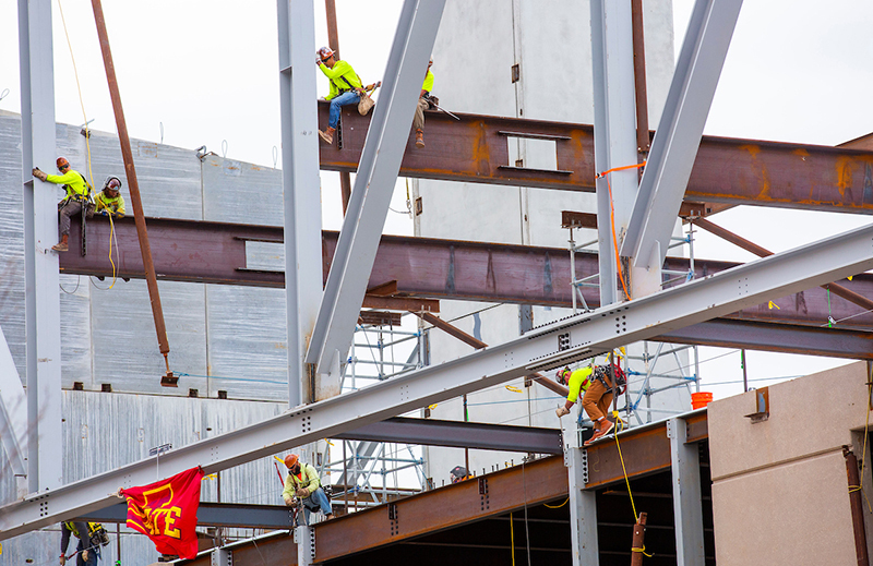 Welders connect the first truss points to the building