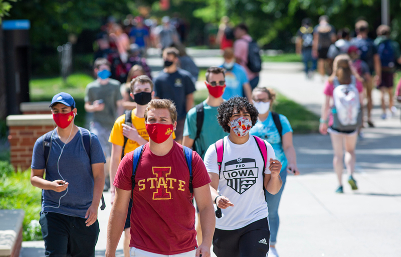 Masked students walk on central campus