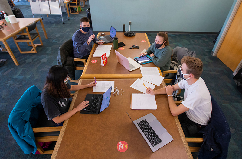Four students study physically distanced in the libary