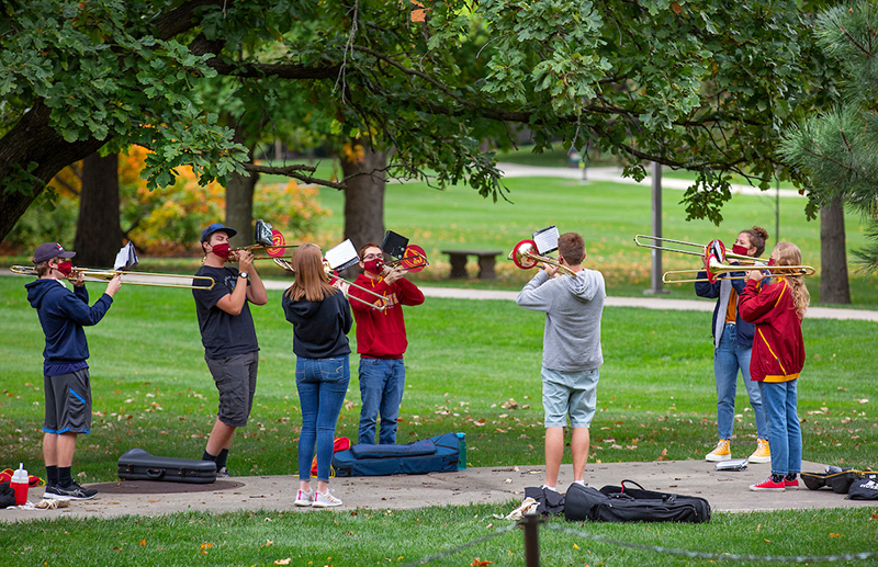 Marching band trombonists practice on central campus