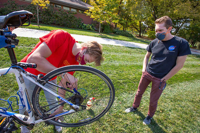Male student tunes up another student's bike near Jischke Hall