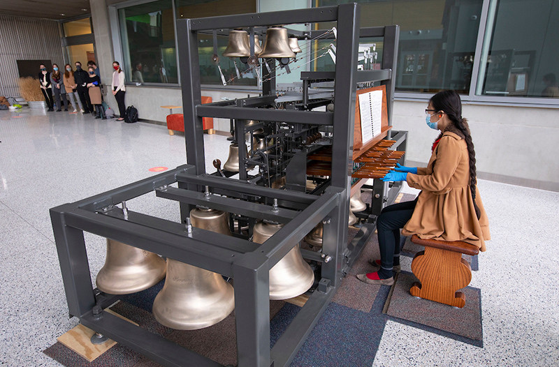 female student plays on carillon model