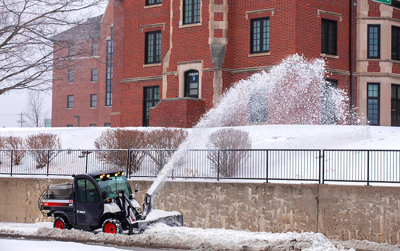 Campus services plow widens the path on a sidewalk south of Fril